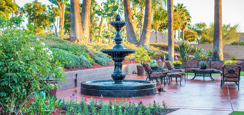Beautiful 3-tiered outdoor fountain with comfortable cushioned seating and mature palm trees