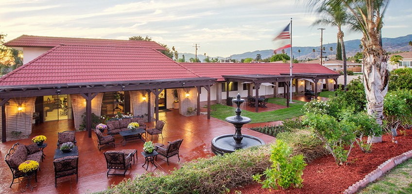 Exterior of Highland Palms featuring a fountain, comfortable outdoor seating, a covered shaded area, and mountains in the background