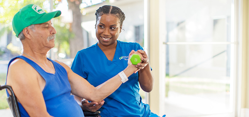 Physical therapist assisting a resident using hand weights for therapy