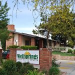Wellsprings entrance sign with parking and lush trees out front
