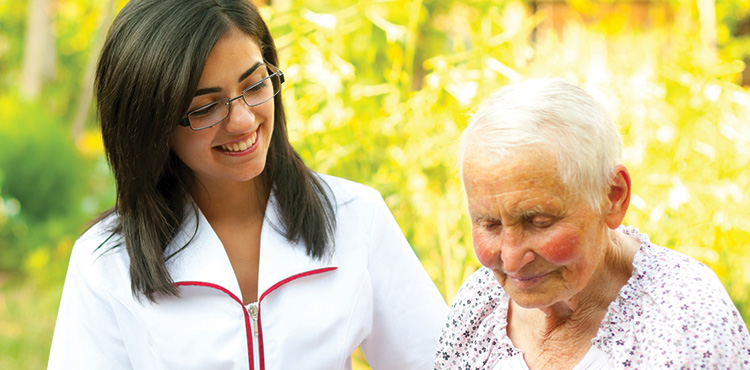 A nurse walking with a resident outdoors