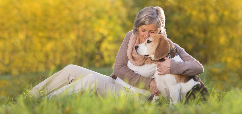 woman hugging her dog in a grassy field