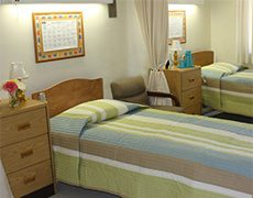 Double occupancy room with nicely made beds and an activity calendar overhead