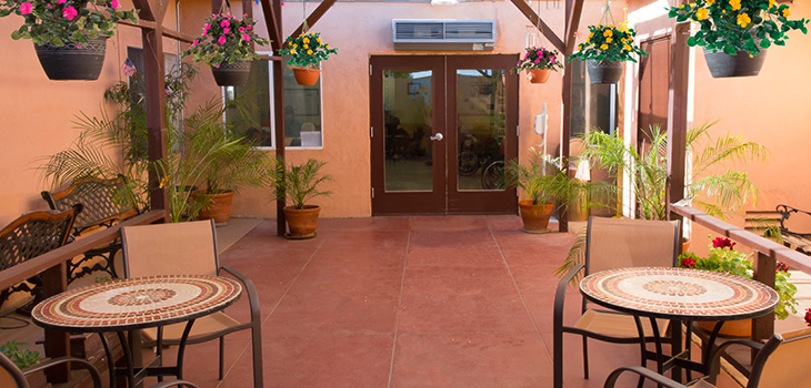 Patio area of the community with seating and hanging plants overhead