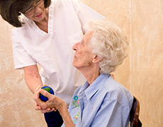 Nurse assisting a resident with holding an exercise ball
