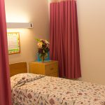 A resident bed with flowers by the bedside and an activity calendar posted overhead