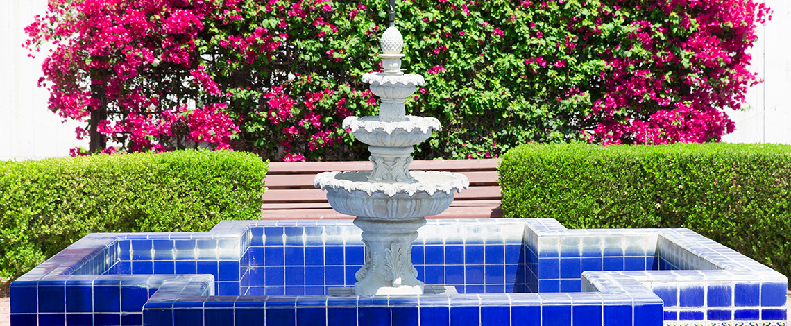 beautiful outdoor fountain surrounded by manicured hedges and bougainvillea vines