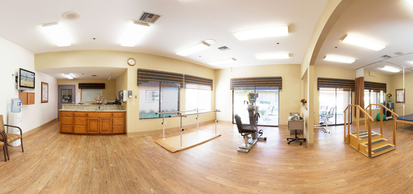 rehabilitation room with various pieces of equipment and large windows