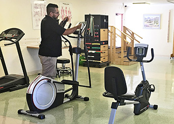 staff member maintaining exercise equipment