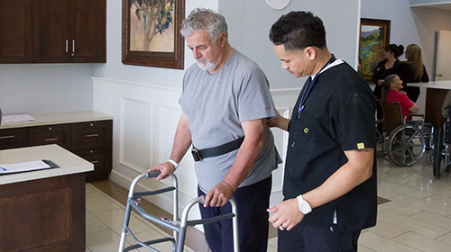 male resident using a walker with a therapist