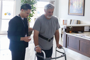 resident using a walker and talking to therpist