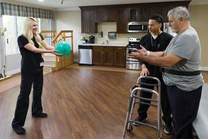 therapist tossing a therapy ball to resident