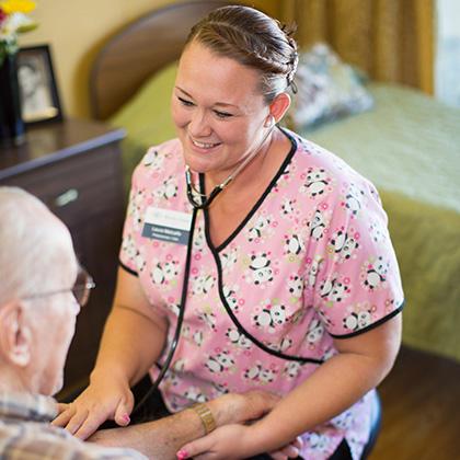 nurse in scrubs taking resident's vitals