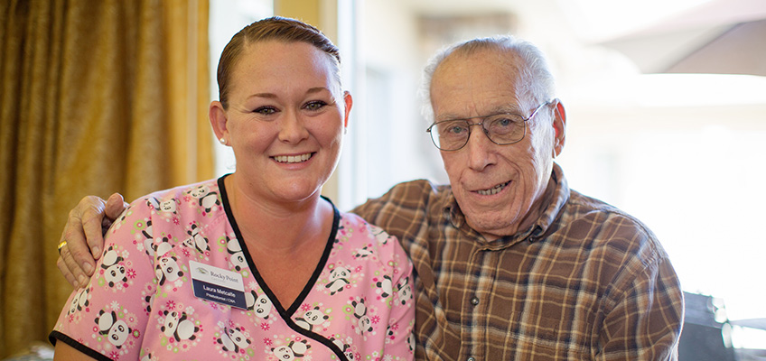 elderly resident with arm around nurse in scrubs