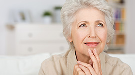 woman with hand on face looking thoughtful