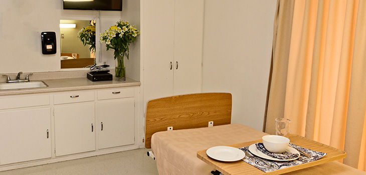 A resident room with a decorative food tray and flowers by the sink