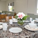 Resident dining area with a beautiful lily centerpiece and decorative table covers with plates and cups neatly arranged