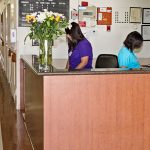 Nurses station with two nurses inside actively working