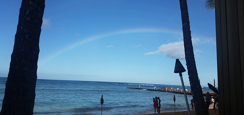 Image of a beach with people walking around the shore line and a pier with a rainbow overhead
