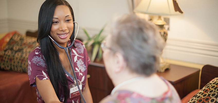nurse with stethoscope taking resident's vitals