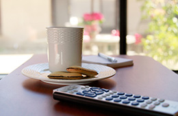 a cup of coffee and cookies with a television remote on a bed table