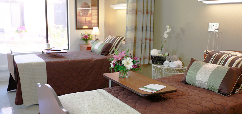 beds with nicely covered pillows, and flowers in the bed tables