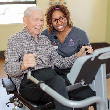 nurse encouraging resident using exercise equipment