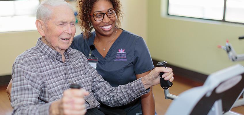 nurse encourage resident using exercise maching
