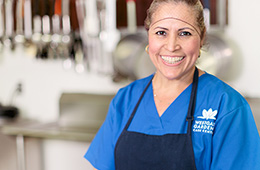 kitchen staff smiling and wearing a hairnet