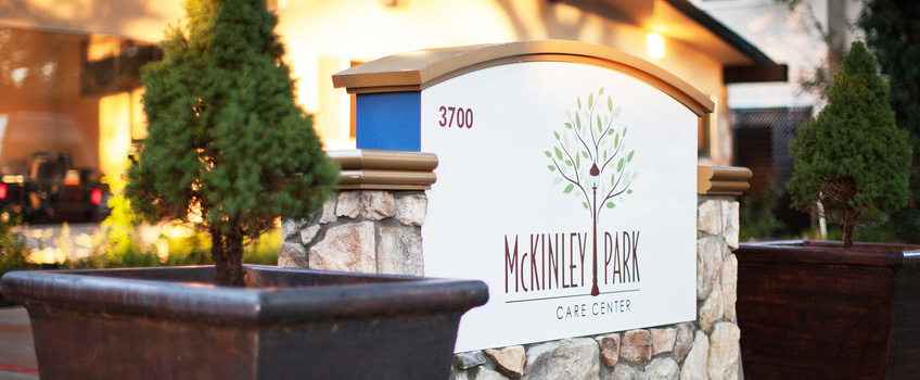 McKinley Park Care Center sign out front with planted trees on each side