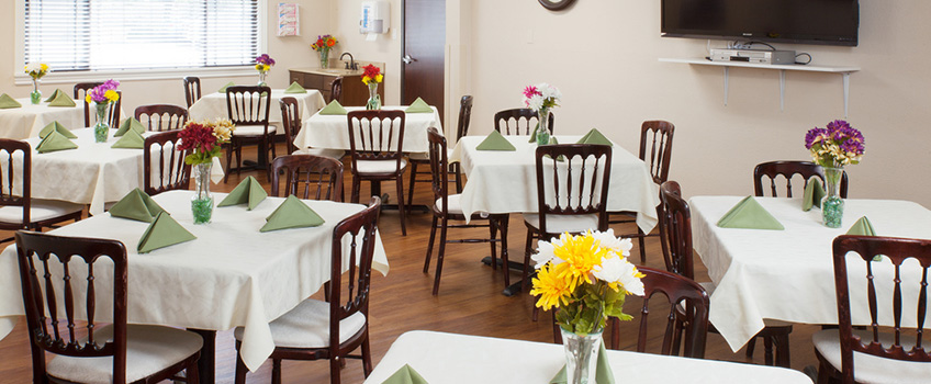 resident dining area with tables set with decorative napkins and flowers