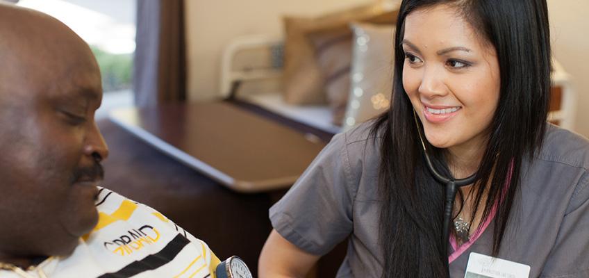 Nurse smiling while taking residents blood pressure