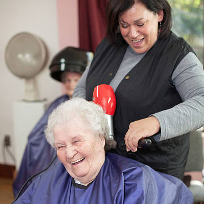 salon staff and resident laughing while salon team member blow drys residents hair