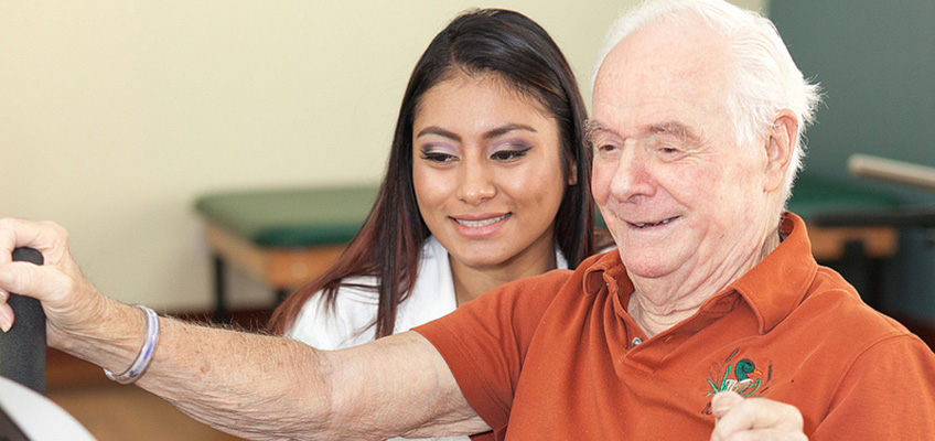 staff member with resident on rehab equipment