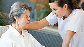 nurse bending down to speak with resident