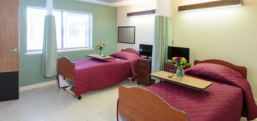 A double occupancy room with personal televisions on the night stand and flowers on the meal tray