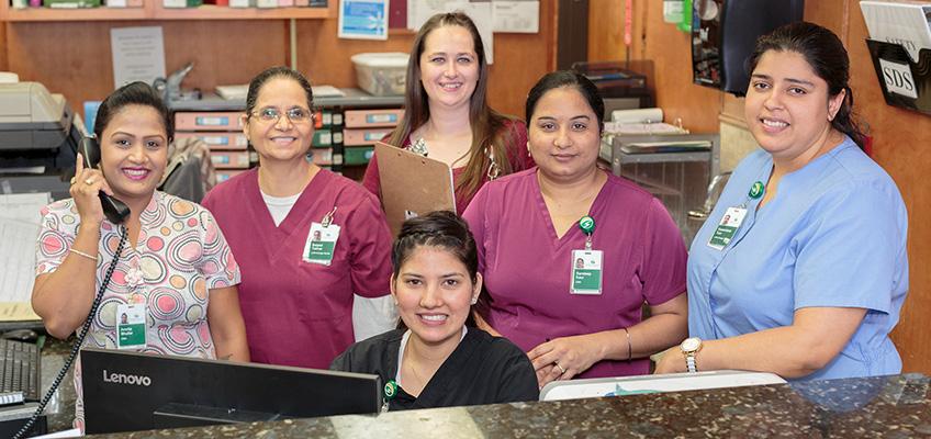 Nursing staff smiling together in the nurses station