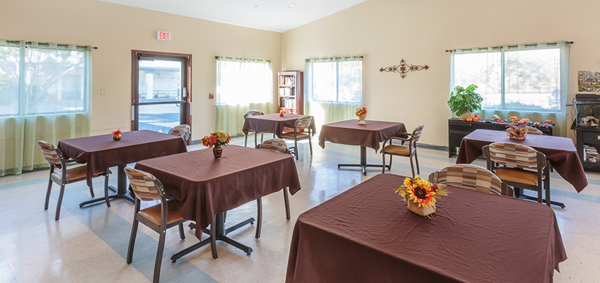 Resident dining room with table cloths on each table and flowers in the center