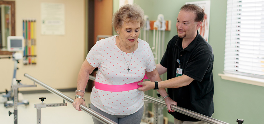 Rehabilitation staff member assisting a resident with walking using parallel bars and a support strap