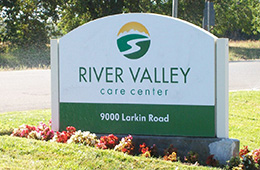 River Valley Center sign out front with flowers and grass surrrounding it