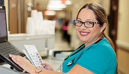Nurse smiling while inputting resident information onto a computer