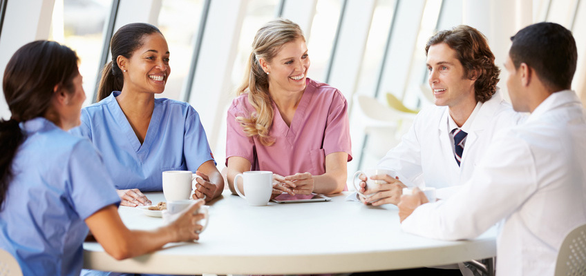 doctors and nurses sitting around a table with coffee, smiling and chatting