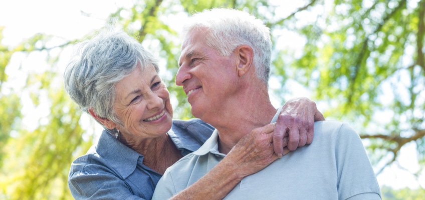 elderly couple smiling and hugging with green tree leaves in the background