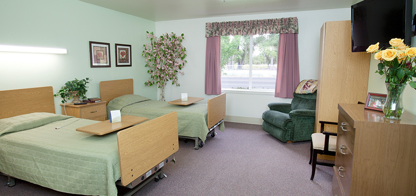 a two bed room, with flowers on most surfaces, bedside tables, cabinets and seating
