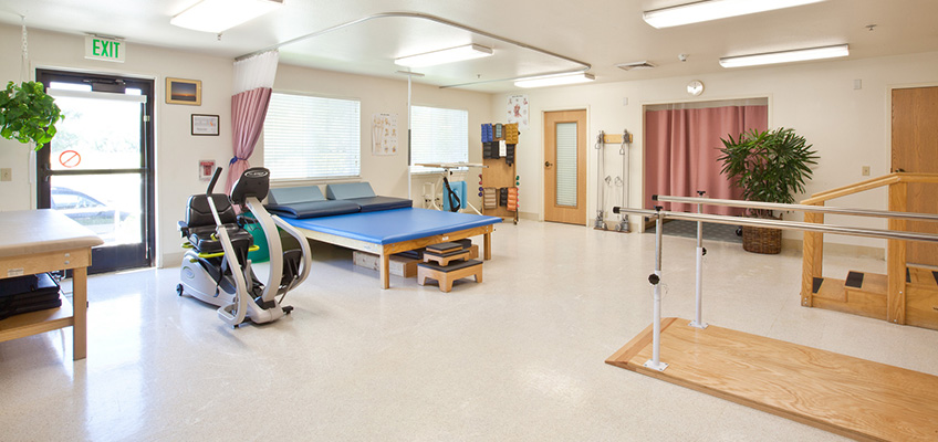 rehabilitation room interior with parallel bars, stairs, bikes and various pieces of equipment