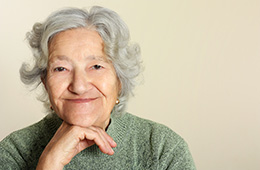 smiling elderly woman with chin on her hand