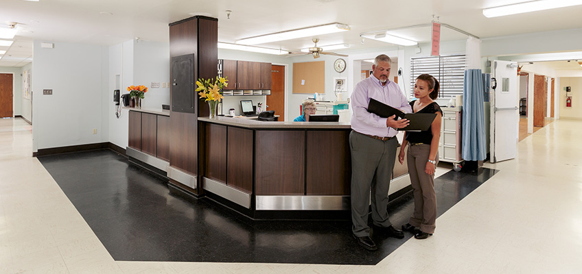two employees consulting at front desk
