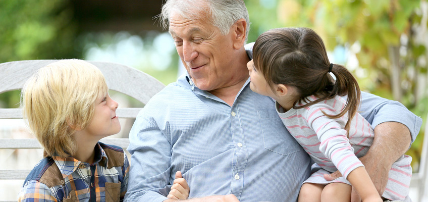 smiling grandpa with grandkids on park bench
