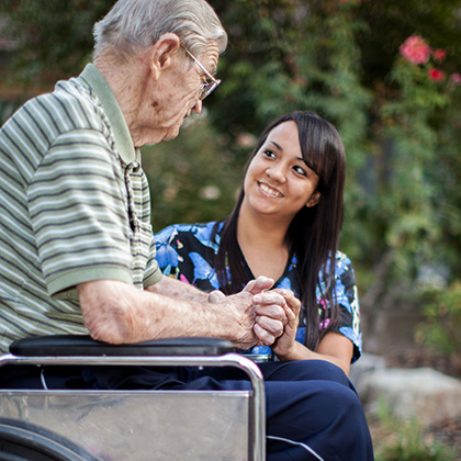 Nurse smiling with resident in wheel chair