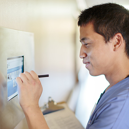 Nurse inputting information on a digital screen